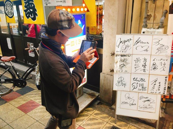 飾られている芸能人のサインを撮る横ちゃん
