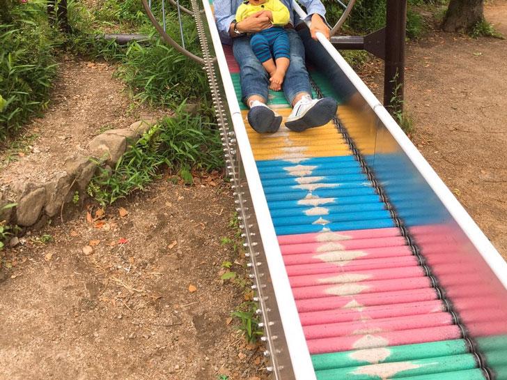 滑り台をすべる親子