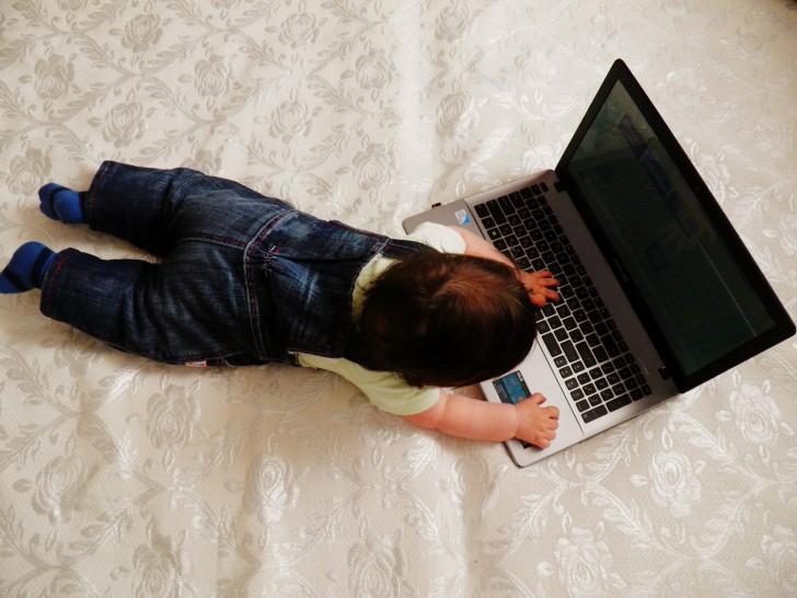 子どもがパソコンを触ってる写真